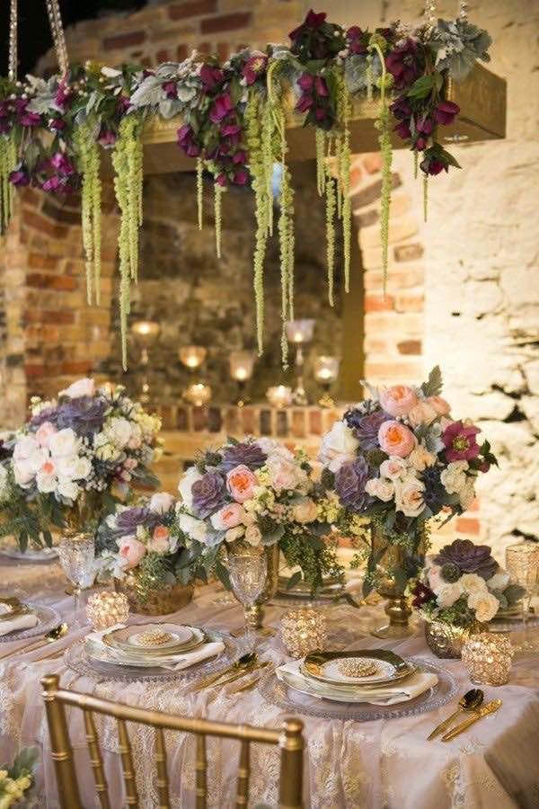 Cuelga helechos de una madera y agrega un pop of color arriba de las mesas de tu boda. Decoración de bodas con centros de mesa colgantes.
