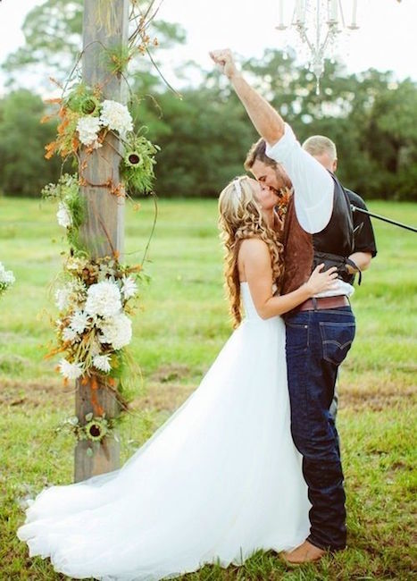 Perfect rustic wedding decoration. Una decoración perfecta para una country wedding con luces colgantes, un poste rodeado de flores y un novio con botas vaqueras y jeans.