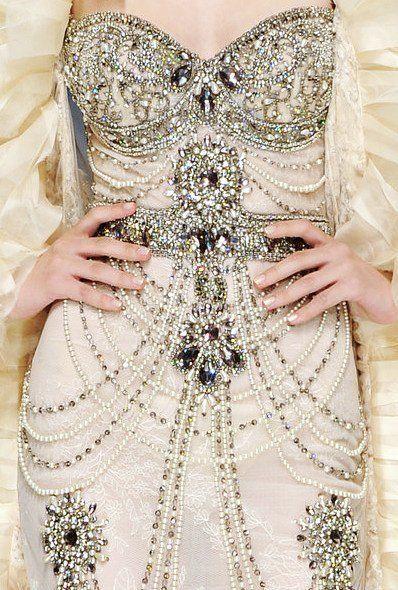 Detalle de un vestido bordado con perlas y joyas.