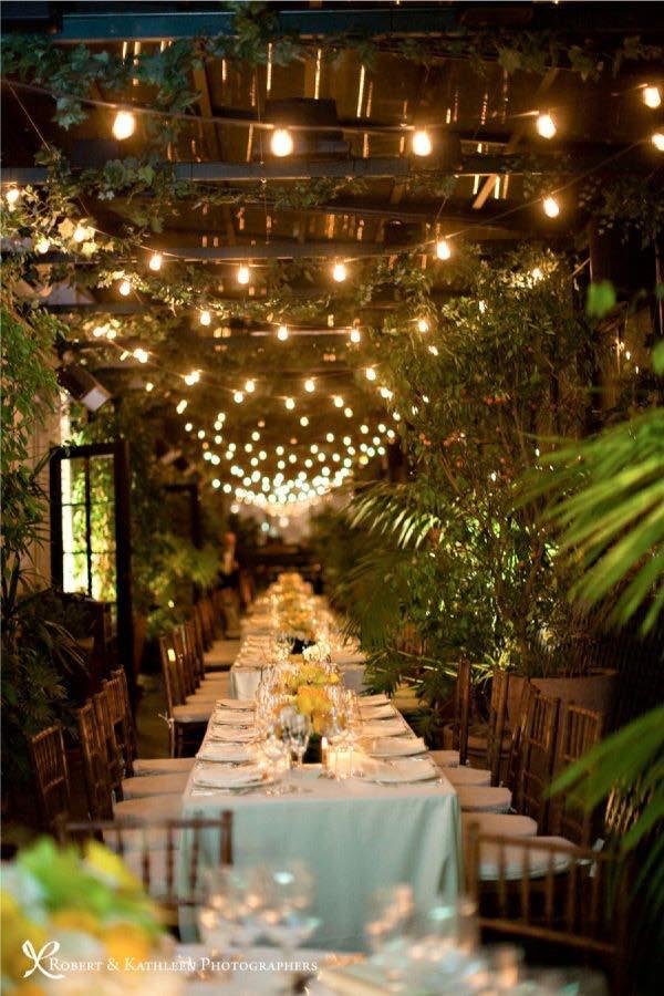 Las mesas largas se merecen centros de boda colgantes con un mar de luces.