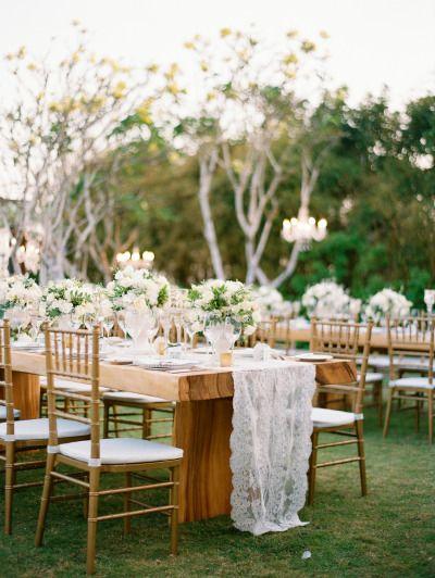 Caminos de mesa para bodas de encaje blanco y largo hasta el suelo le dan un look delicado y con mucha clase a esta boda al aire libre. Fotografía: Angga Permana Photography