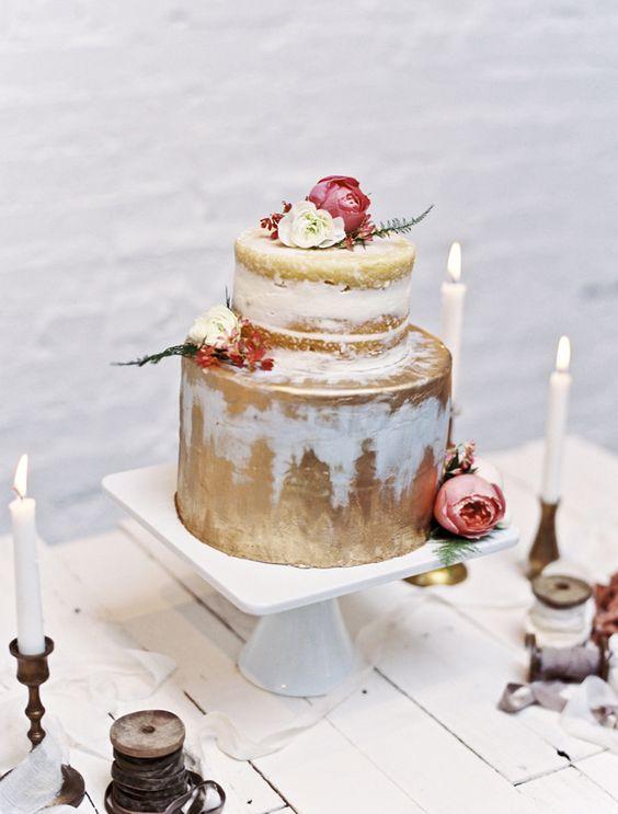 Pastel con crema de mantequilla o skimmed buttercream pintada en dorado, de dos pisos, redonda y con peonias en rosa fotografiada por Loblee Photography.