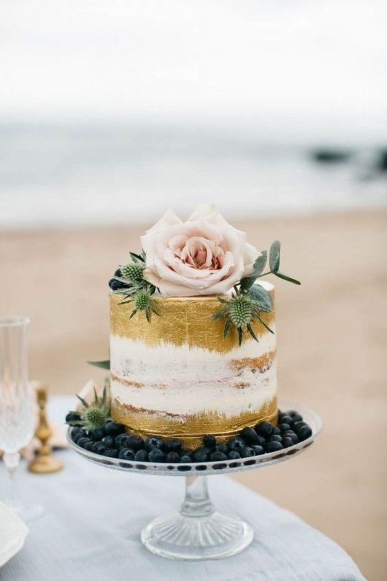 Ideal para una boda en primavera. Pastel de bodas semi-desnudo con dorado pintado a mano, fotografiado por Paula McManus Photography. Presentado en un lecho de blueberries, con un topper de una rosa y cardos en flor.