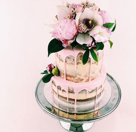 Tarta de bodas semi-desnuda con impactantes y deliciosos colores rosas y un topper de flores naturales que juegan con los tonos de la tarta.