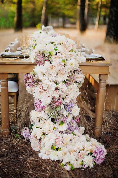 Una guirnalda de flores cubriendo la mesa de bodas. ¿Te la imaginas bajo una carpa decorada con luces?