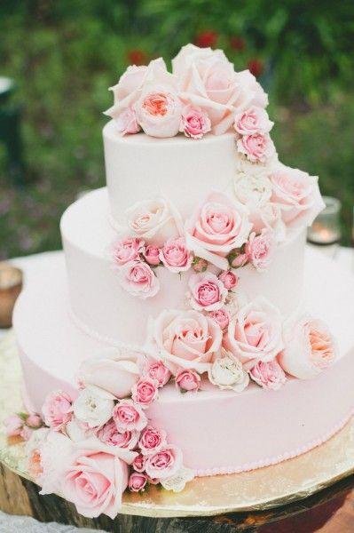 3-tiered wedding cake with a cascade of roses. Un pastel de bodas de tres pisos con una cascada de rosas.