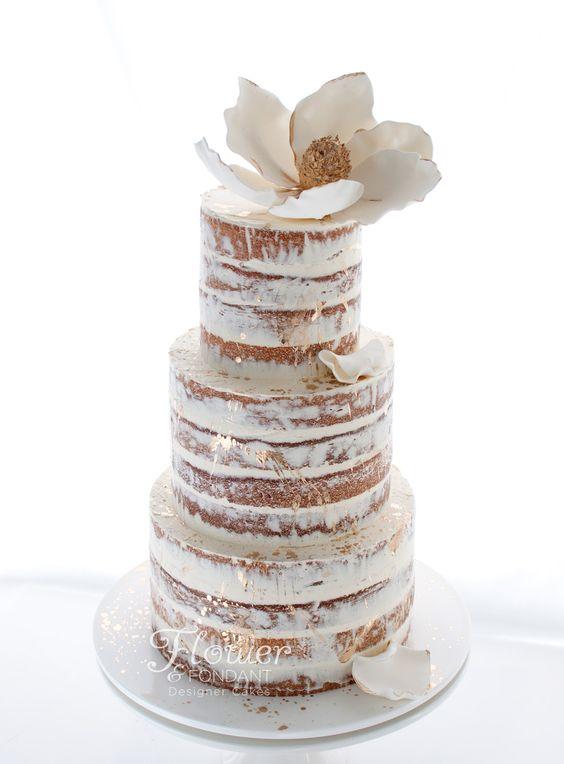 Una creación de Flower and Fondant. Una fantasía en blanco y dorado con el acento de una magnolia que adorna esta tarta semi-desnuda. Sus sabores son vaina de vainilla o vanilla bean buttercake y buttercream o crema de mantequilla merengue italiano con vainillina.