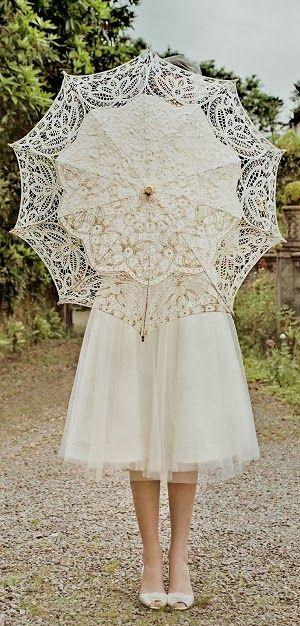 Un look vintage, romántico y elegante en estos vestidos de novia cortos con encajes y sombrilla o parasol.