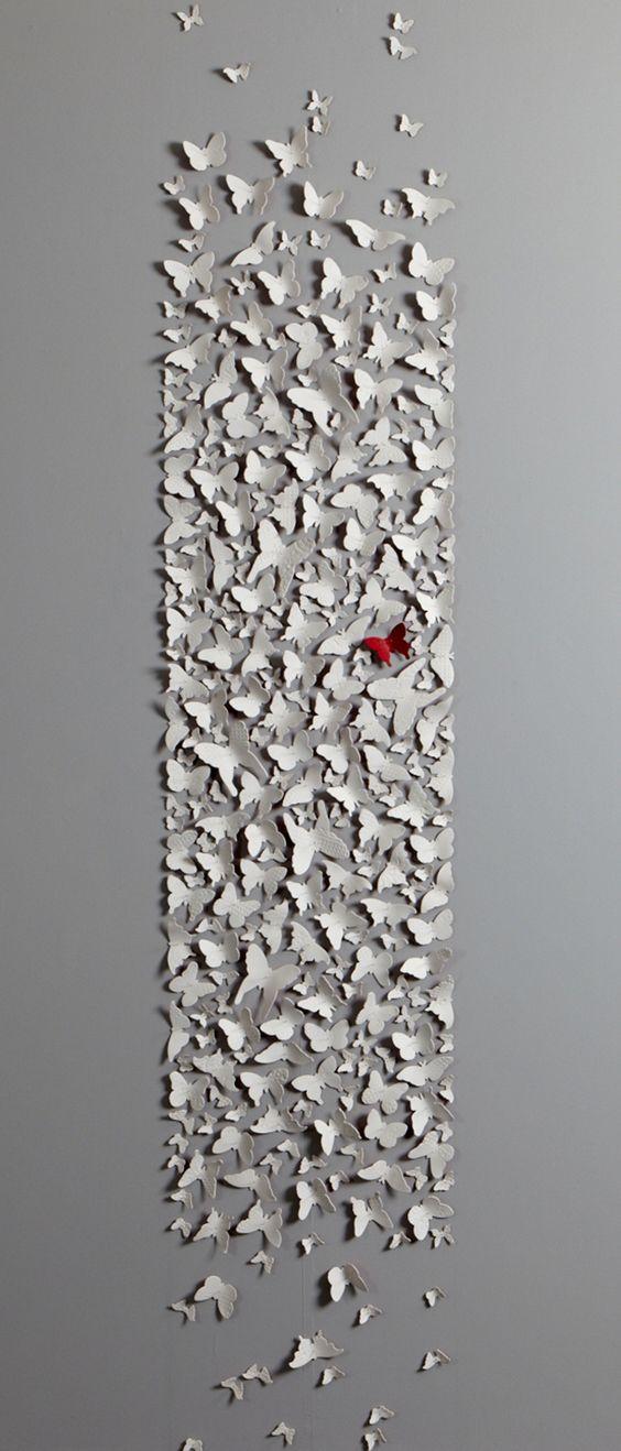 Cómo hacer cortinas de papel para bodas con mariposas. Arma mariposas de distintos tamaños y distribúyelas en la pared. Pinta una de las mariposas en el color de tu boda.