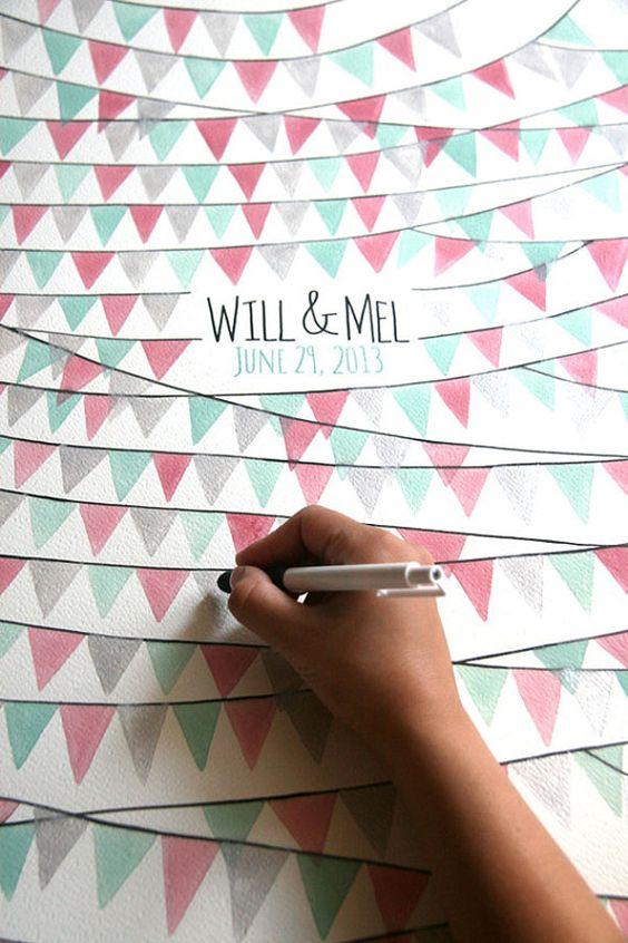 Un poster con banderitas en los colores de tu boda como libro de firmas para boda. Personalízalo con los nombres de los novios y la fecha de la boda y enmárcalo.