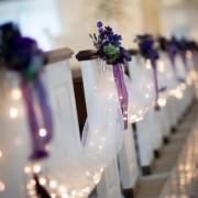 Como decorar el pasillo central de la ceremonia de bodas. Drapeado en tul blanco, mini-luces blancas, arreglos florales en seda morados con hojas verdes y cintas violetas con lazos. Pristine Chapel, Sacramento, CA.