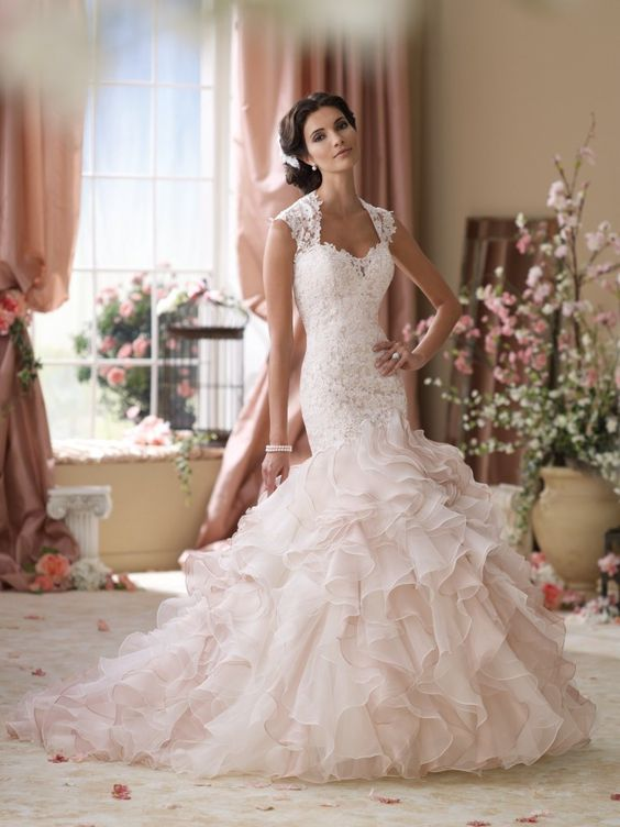 Delicate hand-beaded lace appliqué, softly curved, pleated neckline, gorgeous three-dimensional floral motifs, very 2016, luxurious and exquisite fabrics the latest collection of David Tutera wedding dresses for Mon Cheri Bridals is just so drop-dead gorgeous.