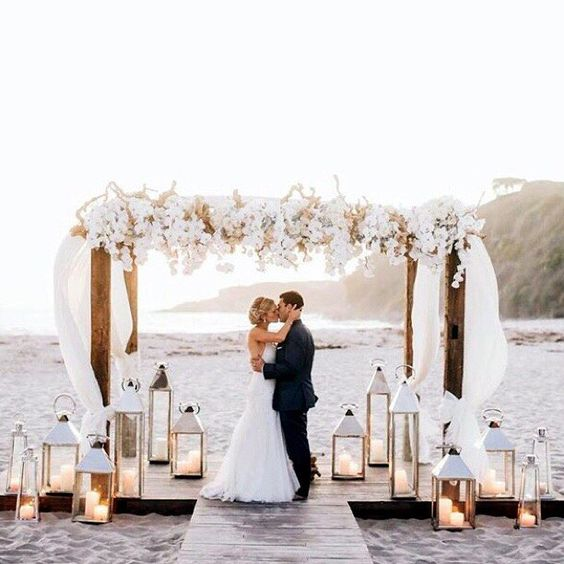 Flowers and lanterns with risers in the sand.