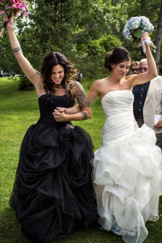 Tracey Buyce Photography captured a perfectly loving moment at this LGBT wedding. The brides wear a black and a white wedding dress.