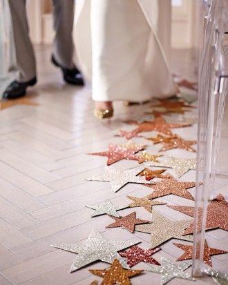 Arma tu propio camino al altar radiante de estrellas. Espolvorea purpurina sobre las estrellas de papel y pégalas con cinta adhesiva en el pasillo central. Estrellas de papel de aluminio troqueladas en 5, 9, y 12 pulgadas.