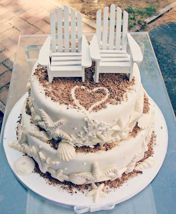 Romantic beach themed wedding cake design with sun, love and seashells in gorgeous white.