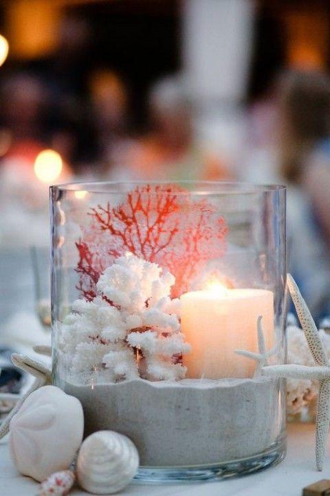 Un centro de mesa encantador: arena, conchas y una vela.