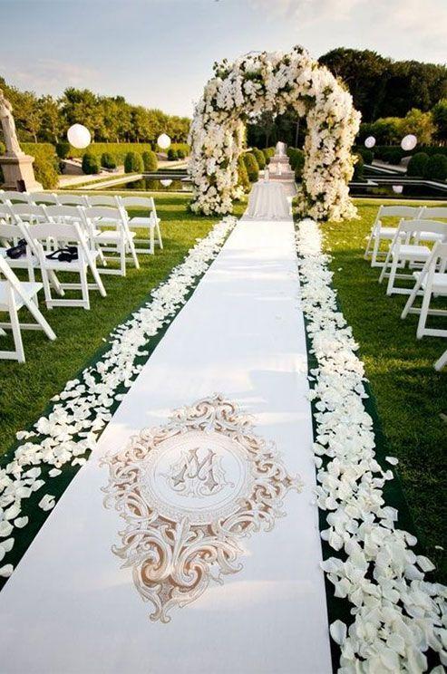 Una alfombra elegante con el monograma de los novios con pétalos a los costados que llevan a un altar con flores blancas.
