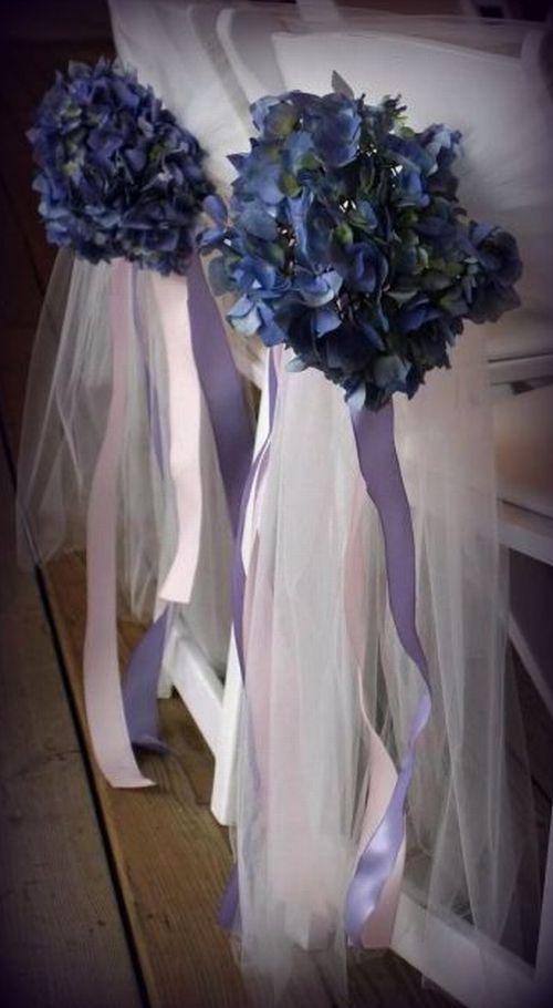 Como decorar pasillos centrales de ceremonias. Sillas con pops de flores azules y cintas violetas colgando de las mismas.