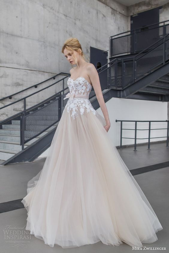 Mira Zwilinger bridal. Fiona strapless, blush, layered tulle wedding dress with white hand embroidered guipure flowers, and organza bow belt in the front.