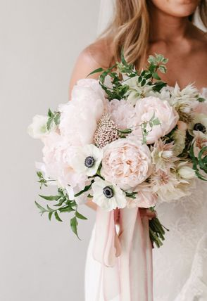 Decoración de una boda romántica en blush: Un ramo de novia con rosas pálidos y tonos en crema con peonias y cintas para una perfecta blushing bride.