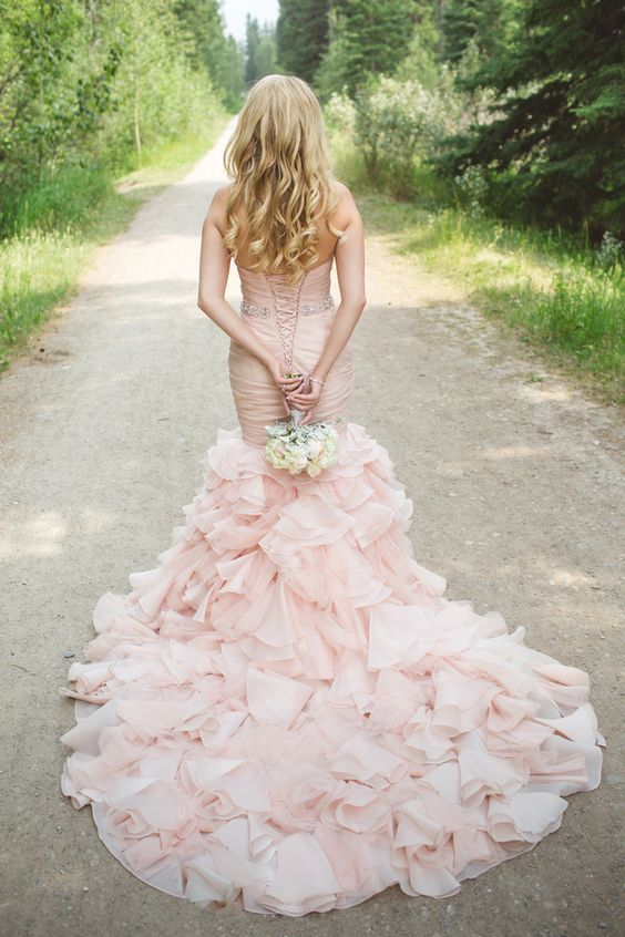 A ruffled blush wedding dress looks absolutely stunning amidst the scenery of the Glacier National Park. Photography Janine Deanna Photography.