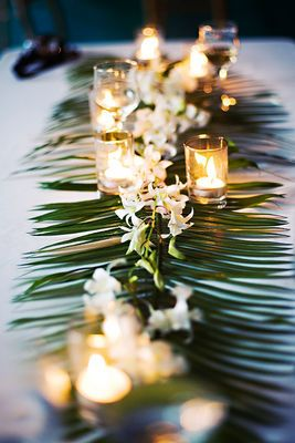 Who said orchids? Well, here you go: a simple but elegant orchid table runner on top of palm fronds for your beach themed wedding ceremony.