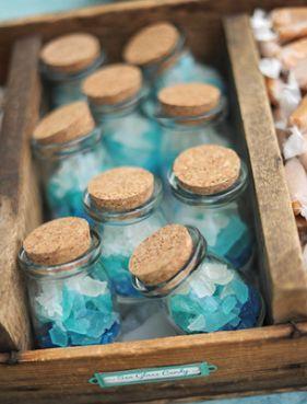 Un buen souvenir para bodas en la playa: unos rock pops azules en frascos con tapa de corcho.