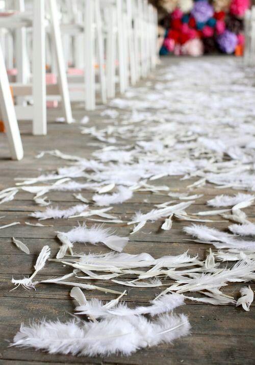 Una boda original muy boho con plumas en lugar de pétalos de rosas.