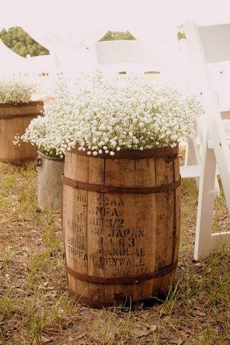 Baby's breath arpillera y encaje en barriles de whisky. Es una forma asequible fácil y bonita para crear un ambiente elegante y romántico para el día de tu boda.
