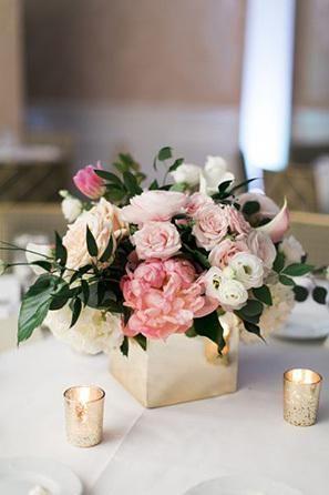 Centros de mesa bajos de boda; arreglos florales tradicionales en floreros bajos. Estas peonías en rosa pastel y rosas en un jarrón cuadrado van bien con las velas doradas para una boda en primavera o verano.
