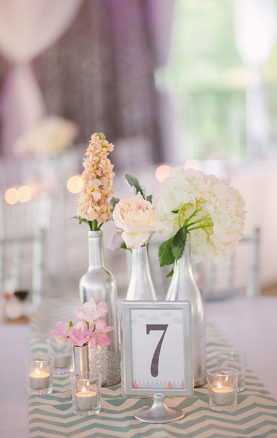 Centros de mesa para una boda industrial. Pinta las botellas en plateado o escoge dorado y úsalas para agregar aun mas glam a tu boda.