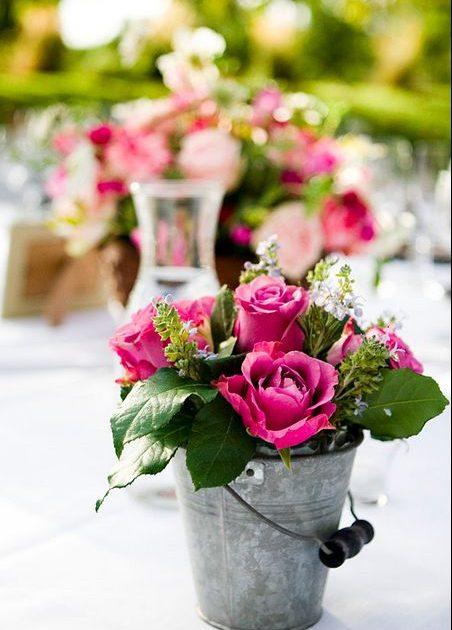 Uno de mis centros de mesa para bodas en verano favoritos: una cubeta con rosas y flores de relleno. ¿Alguien dijo boho chic?
