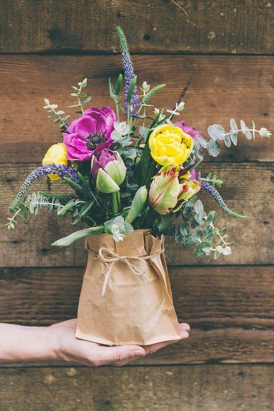 Usa cualquier jarro que tengas y cúbrelo con una bolsa de papel para darle el look perfecto para bodas en jardín. ¡Voila los centros de mesa!