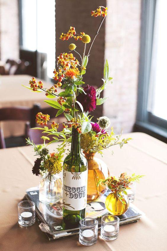 Originales centros de mesa con botellas de vino para una boda veraniega. No olvides agregar el detalle de la etiqueta personalizada.