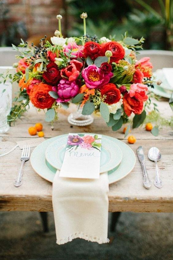 Las peonias causan furor en las bodas de este año y este centro de mesa rebosa de peonias, tulipanes y ranunculus asiáticos que vestirán alegremente una boda en el jardín.