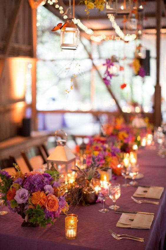 Decoración de una mesa en un granero en Santa Barbara, CA iluminada con velas, fotografiada por Michael + Anna Costa Photographers.