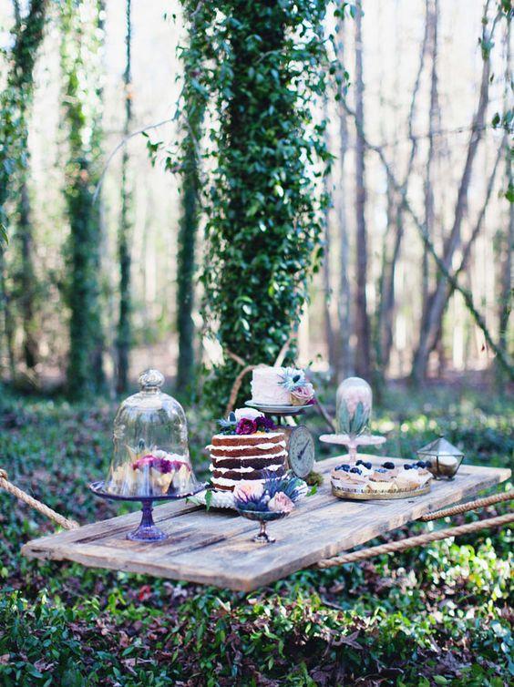 La decoración de mesas para fiestas no se detiene en la de los invitados. Esta mesa de postres en una boda al aire libre es increíblemente original.