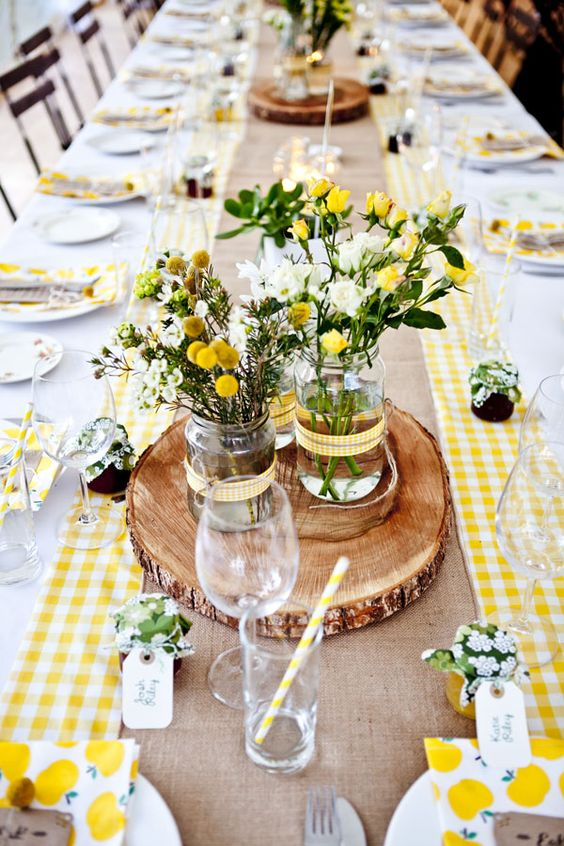 En lugar de manteles dos caminos de mesa a los costados de esta mesa larga detalles rústicos con madera y muchas flores. Try two tablerunners some wooden rustic details and lots of flowers for your table decor.