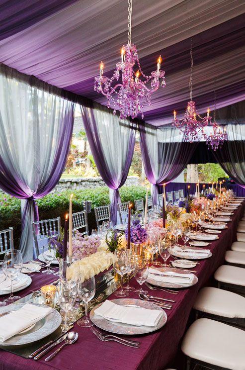 Elegante mesa larga en color marsala que complementa el verde de los jardines para bodas. El drapeado de la carpa, los chandeliers suspendidos sobre las mismas, y las velas altas, le dan ese look refinado. | Elegant purple wedding table, draped curtains and matching chandeliers. Swoon!