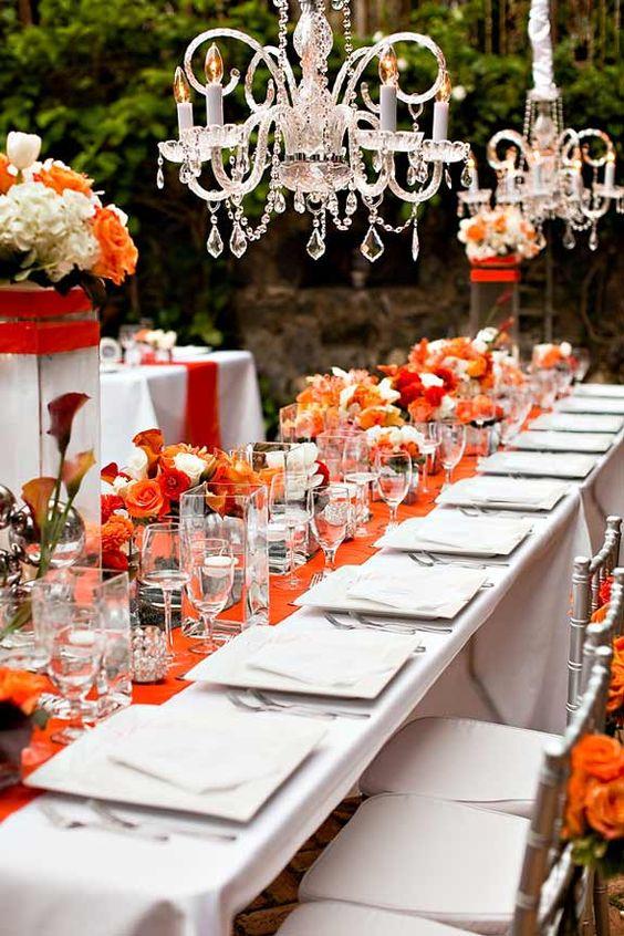 Centros de mesas bajos y chandeliers, sumados a la vajilla cuadrada, le dan un look moderno a esta decoración de mesa larga.