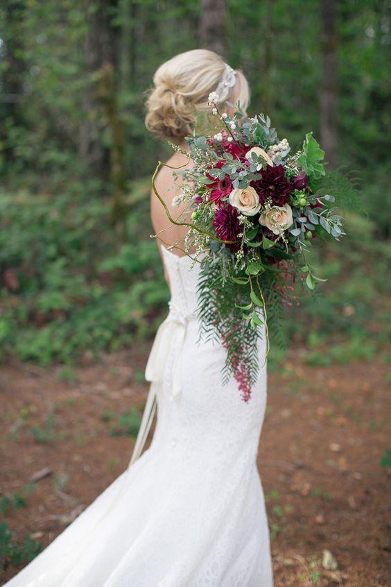 Los ramos de novia se posan sobre los hombros este año. Hermoso ramo en tonos borravino fotografía de Ashley Cook Photography.