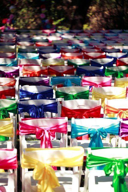 Una inspiración para decorar las sillas en la ceremonia religiosa con los colores del arco iris para este jardín de bodas. | Colorful and fun idea for wrapping the chairs at the ceremony.