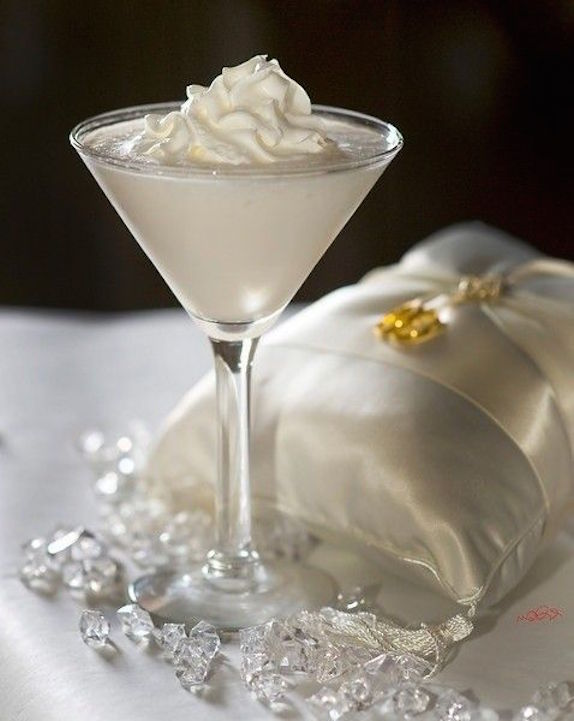 Receta de cocteles para bodas. Wedding Cake Martini hecho con 1,5 onzas de vodka de vainilla 1/2 oz de ron de coco Malibú 1,5 oz de jugo de piña 1 chorrito jarabe de granadina. Cocktail recipe for a Wedding Cake Martini made with 1.5 oz vanilla vodka 1/2 oz Malibu coconut rum 1.5 oz pineapple juice 1 splash grenadine syrup.