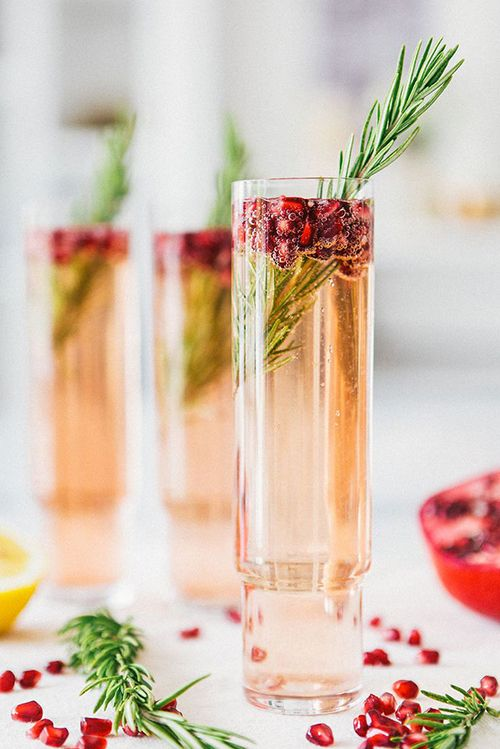 Spritzer de granada y romero. Semillas rojo rubí de granada y una ramita de romero fresco añaden un toque festivo a este coctel a base de Prosecco. Perfecto para una boda en otoño. Pomegranate-Rosemary Spritzer. Ruby red Pomegranate seeds and a sprig of fresh rosemary add a festive touch to this pretty Prosecco-based cocktail. Perfect for a Fall wedding