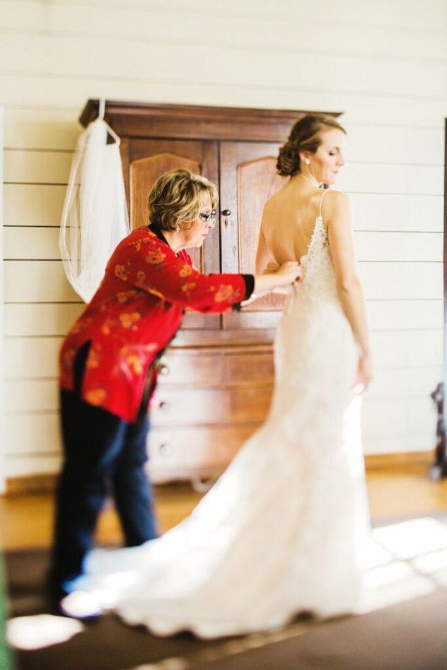 La novia luciendo su vestido de novia con corte trompeta y espalda descubierta.