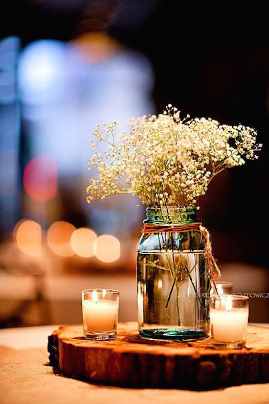 Wedding centerpieces on wooden blocks with baby's breath. Simple and economical.