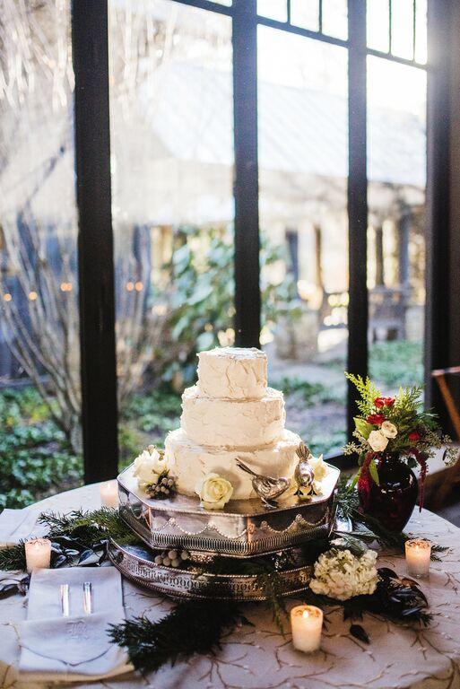 Pájaros en plata representando a los novios posados al costado de la tarta nupcial rústica cubierta de buttercream.