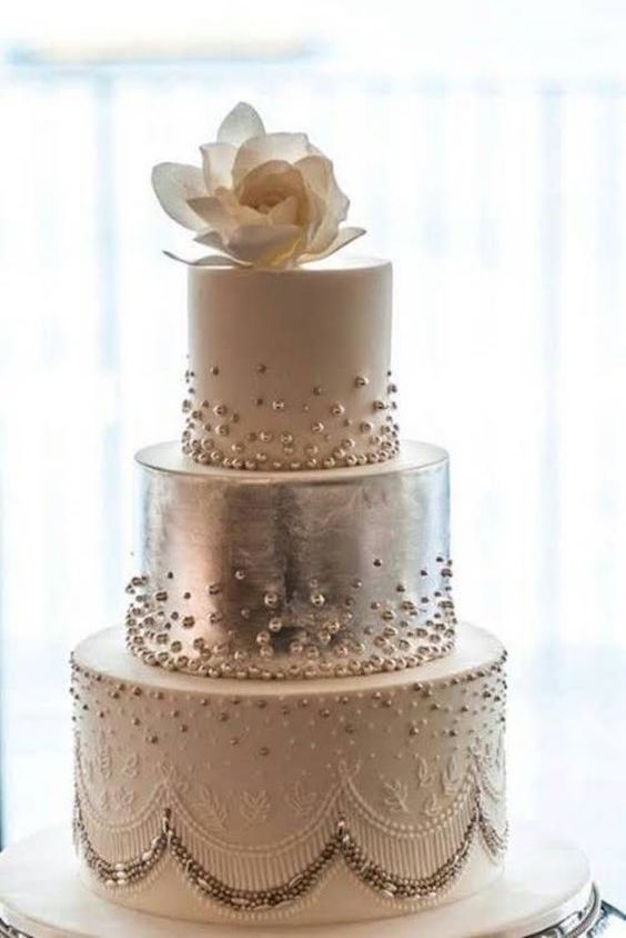 Great Gatsby wedding cake covered in sugar beading. Love the magnolia cake topper.