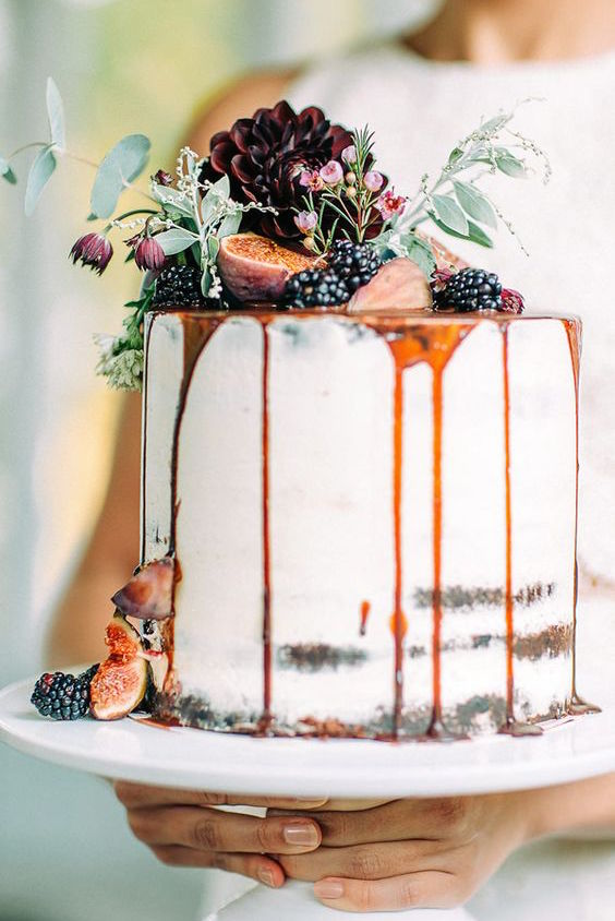 Half dressed wedding cake with fruit and drizzle.